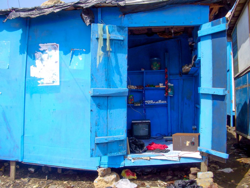 "In overcrowded Old Fadama up to 20 people sleeping on the floor of such a structure like this blue ""kiosk"" on a space of 3 square meters."